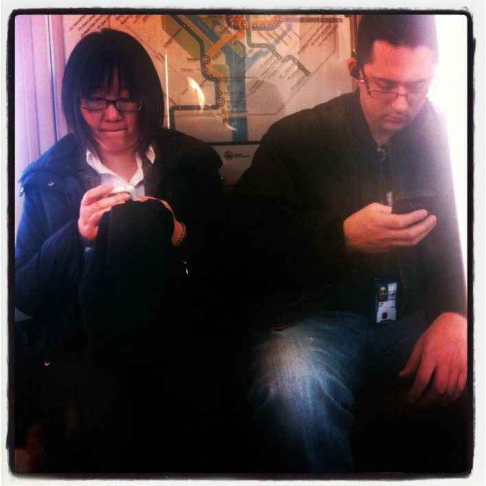 Couple with smart phones on DC metro.