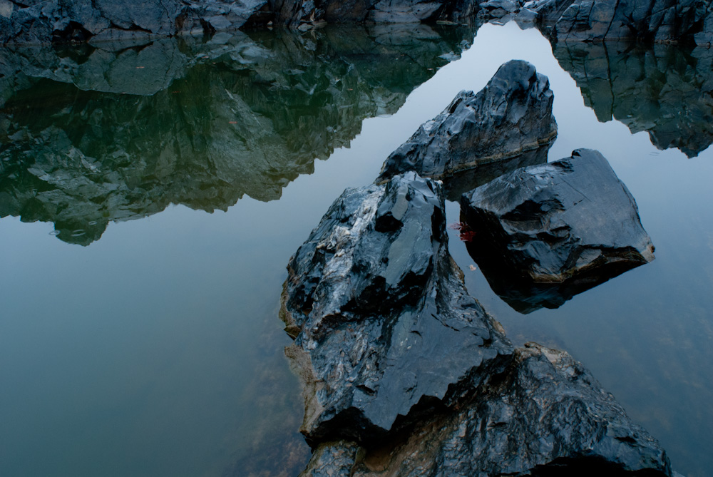 Rock formations and reflections in the calm waters of the Potomac River.