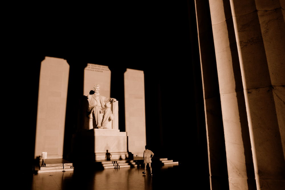 A jogger takes a break and walks up to the statue of Abraham Lincoln inside the Lincoln Memorial. Dawn, Washington DC.