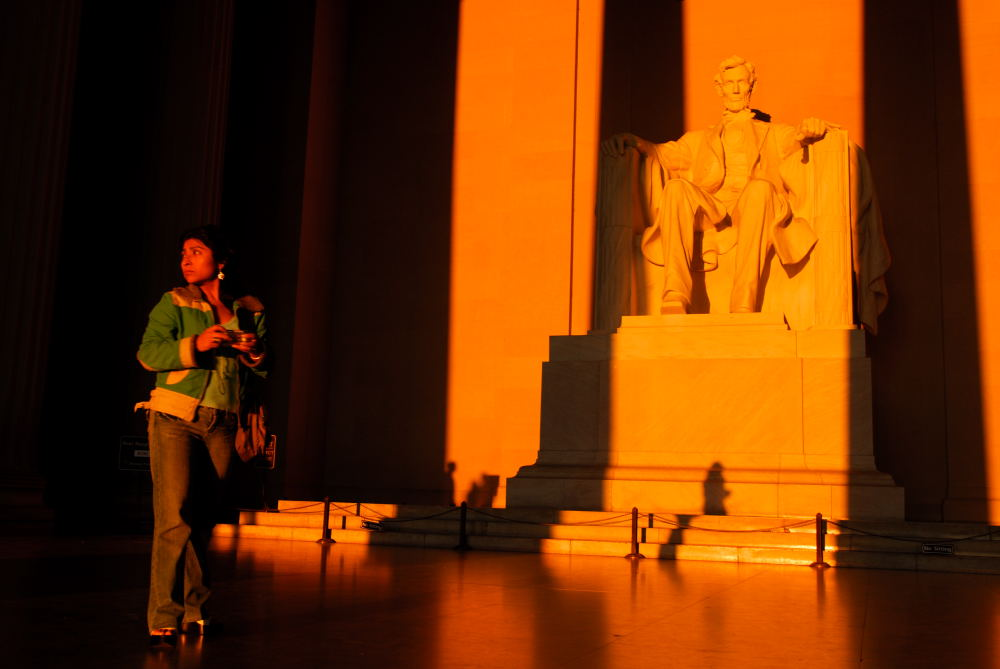 Tourist at sunrise inside Lincoln Memorial, Washington DC.
