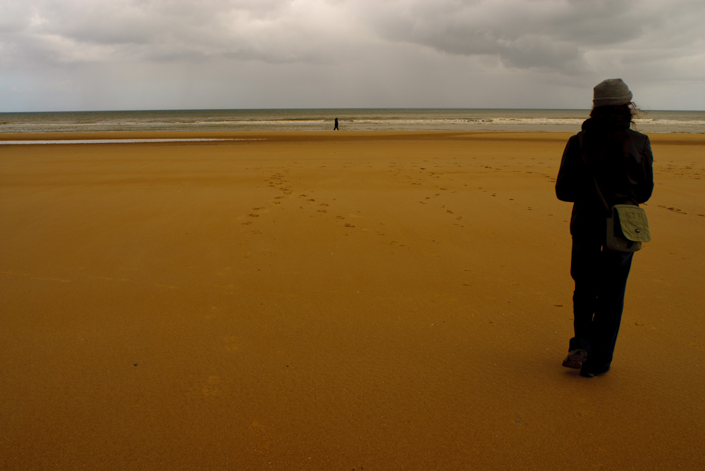 A woman standing on Omaha Beach. An overcast day in Normandy, France.
