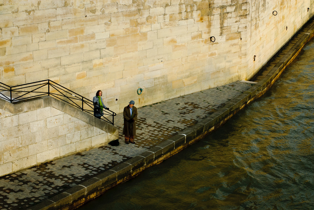 Man and woman walking along the River Seine in Paris.