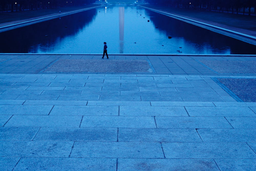 A woman walks past the reflecting pool at the Lincoln Memorial, Washington DC.
