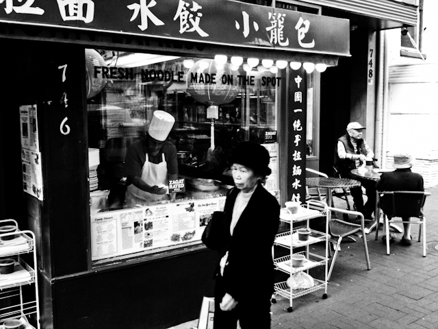 A woman walks past restaurant in Chinatown, Washington DC.