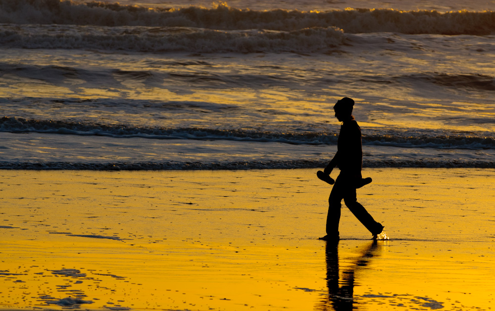 A woman walks the beach at sunset. Stinson Beach.