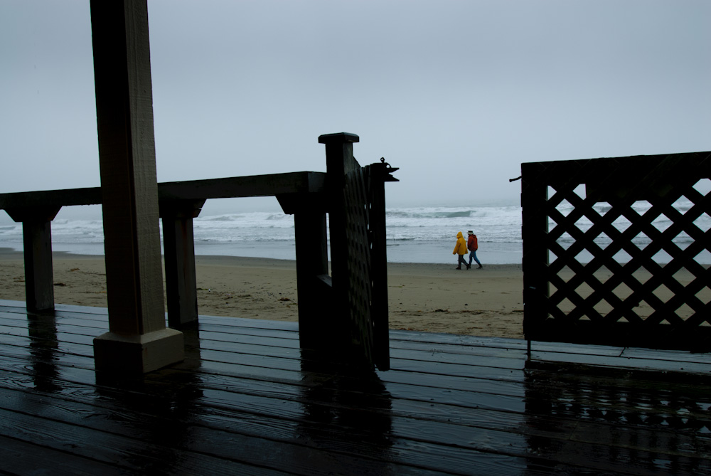 A couple walking the beach in the rain. Stinson Beach.