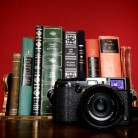 Fuji X100s in front of books. Red background.