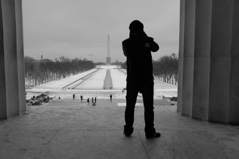 silhouette of man at Lincoln Memorial taking a photo of Washington Monument. Washington DC
