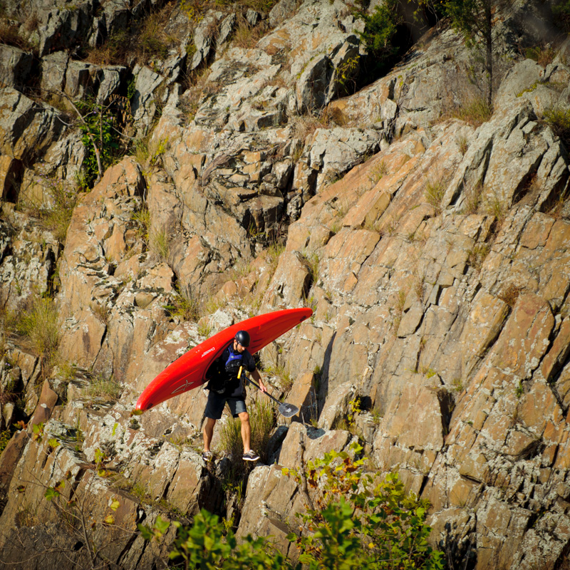 kayaker walking along cliffside. potomac river, great falls