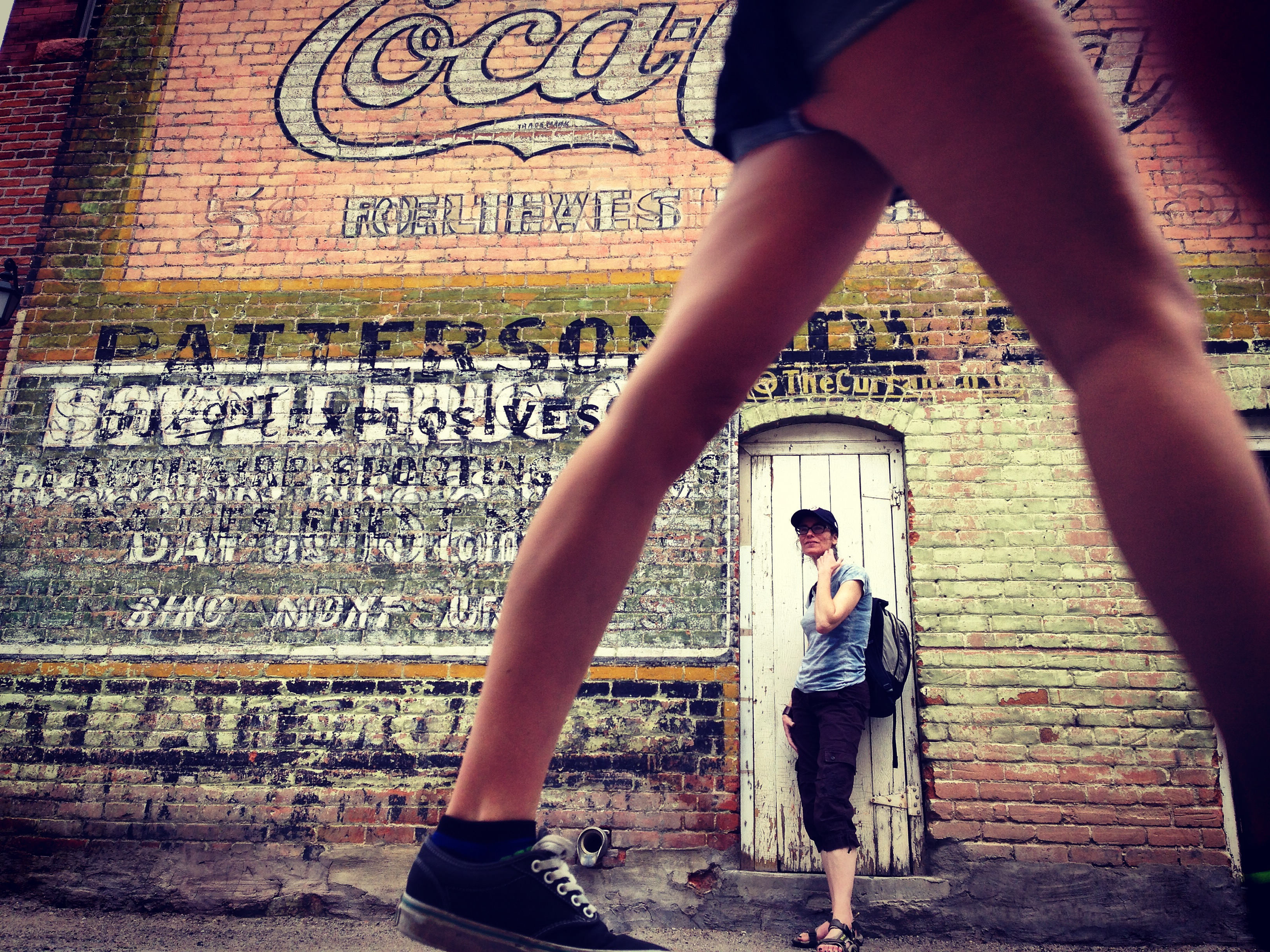two women in salida, colorado. legs and brick wall.