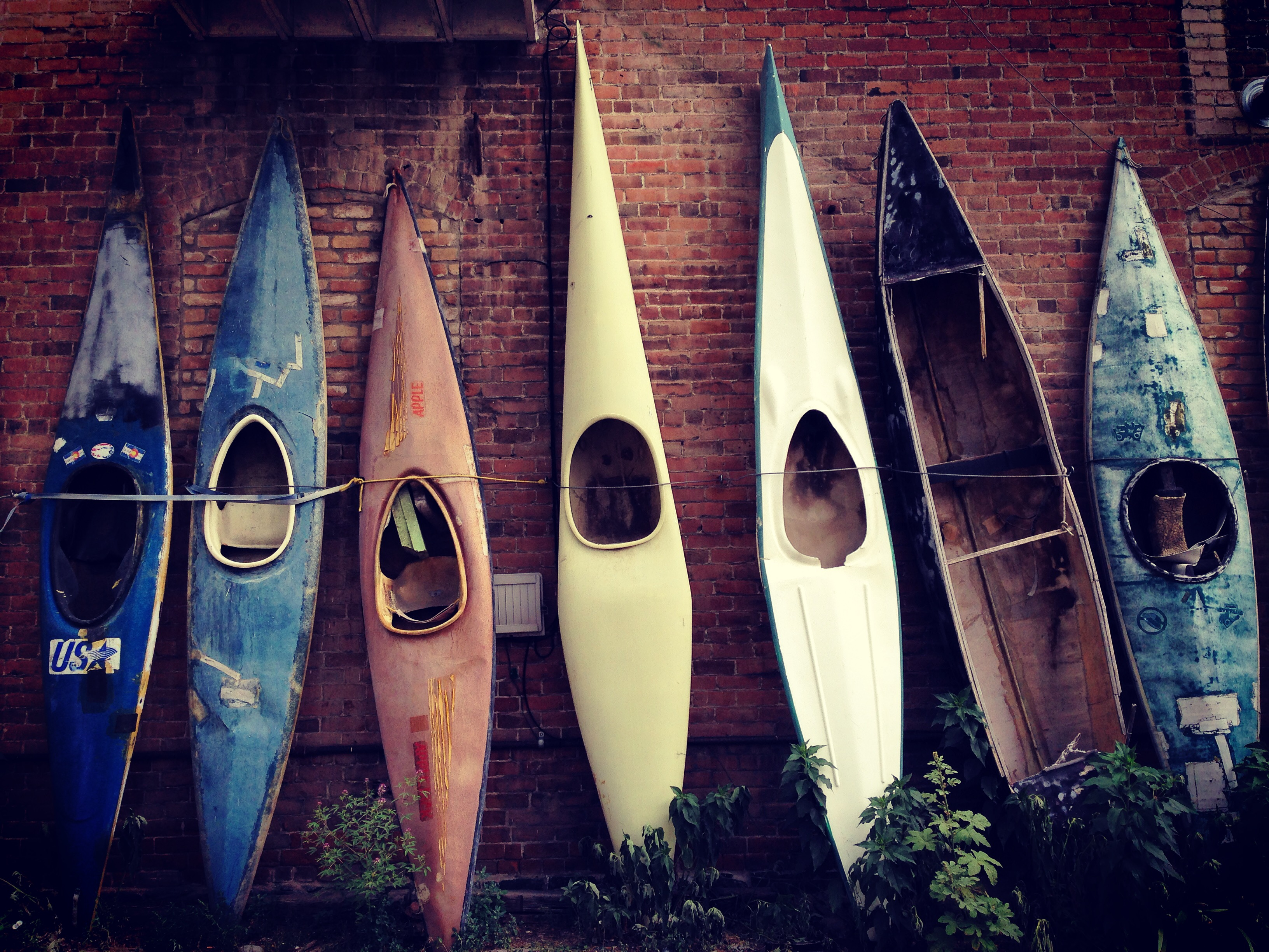 seven kayaks against brick wall in salida, colorado.