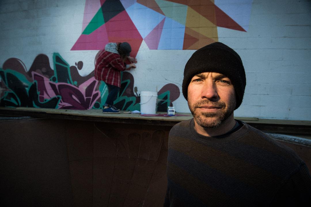 finding a line. Ben Ashworth portrait. wheat paste art piece in background.