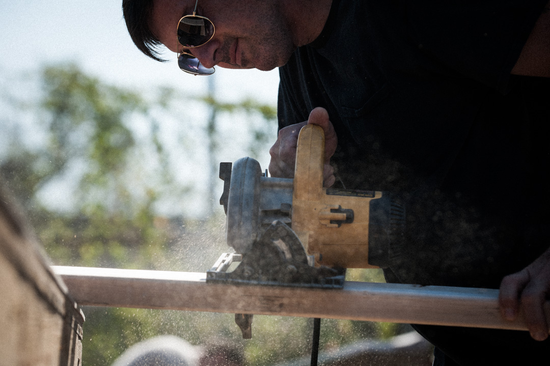 Construction worker cutting a 2x4 with circular saw.