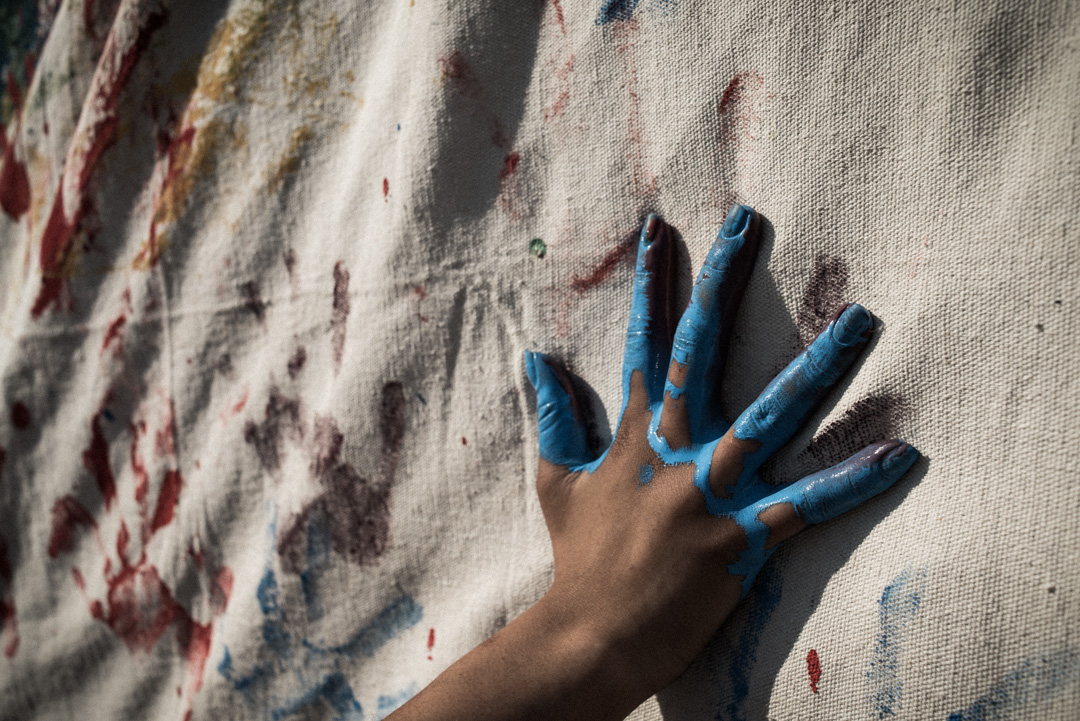 Blue paint on hand. Hand painting white canvas.