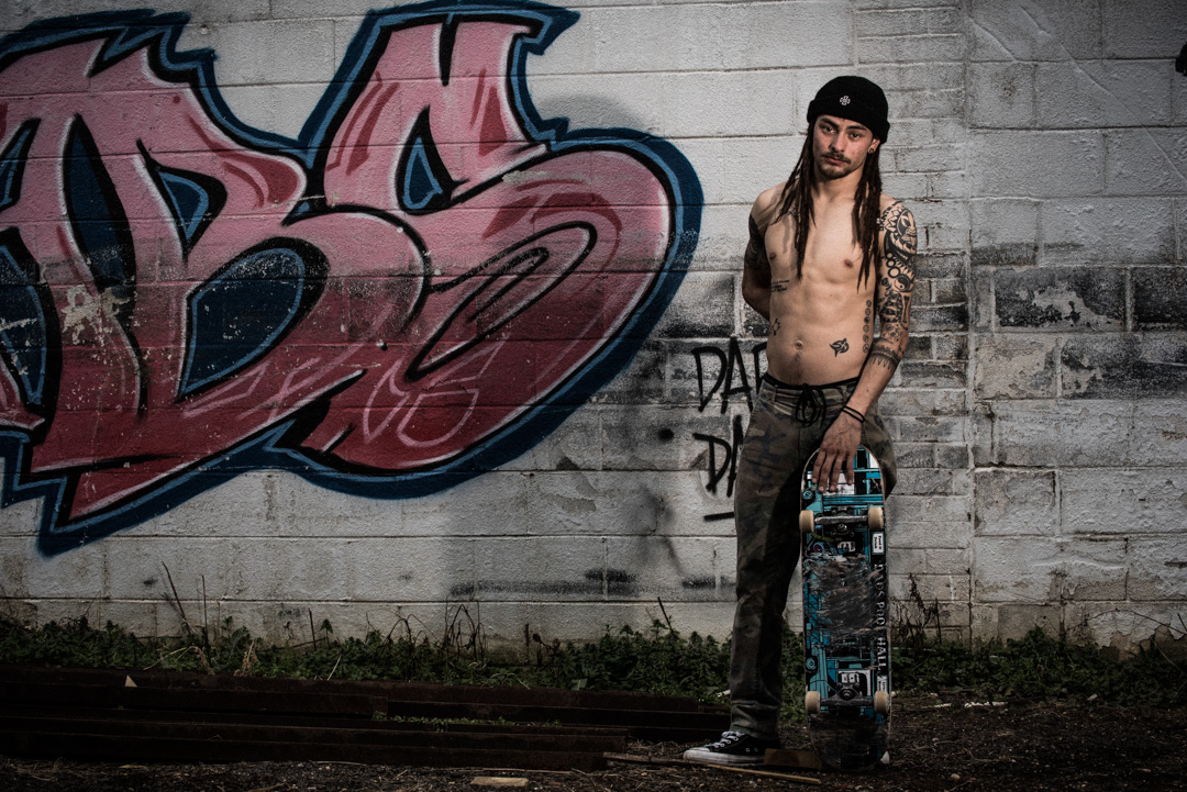 Brandon Lee Padayao shows off his body art next to some wall art. Tattoos and graffiti at the Finding A Line bowl in DC.