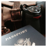 photo of passport and nikon camera, with filson bag