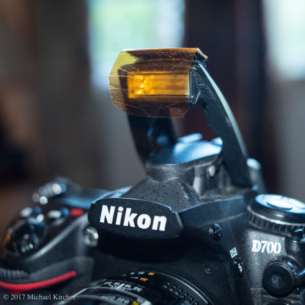 Amber gel affixed to the pop-up flash of a Nikon D700 using custom cut velcro strips.