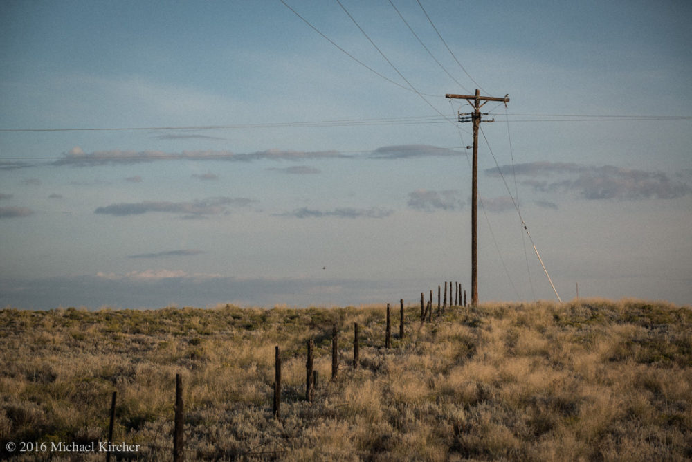 Telephone post, cable and electric wires. On the road, somewhere in Colorado.