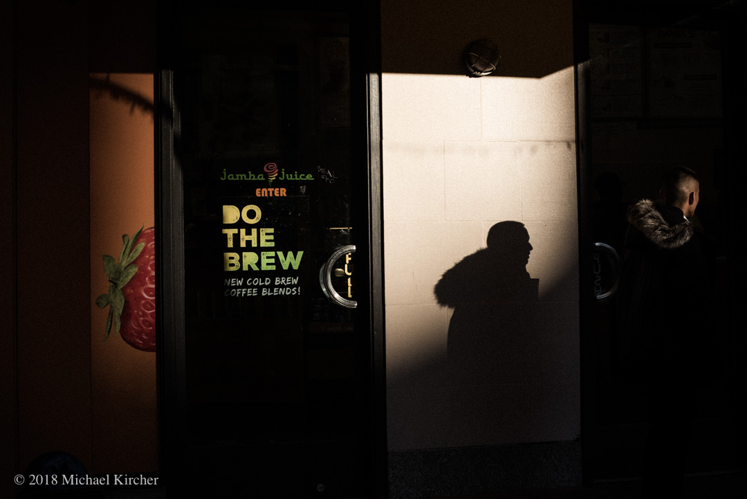 Late afternoon light and shadow of a young man in front of Jamba Juice in Washington DC.