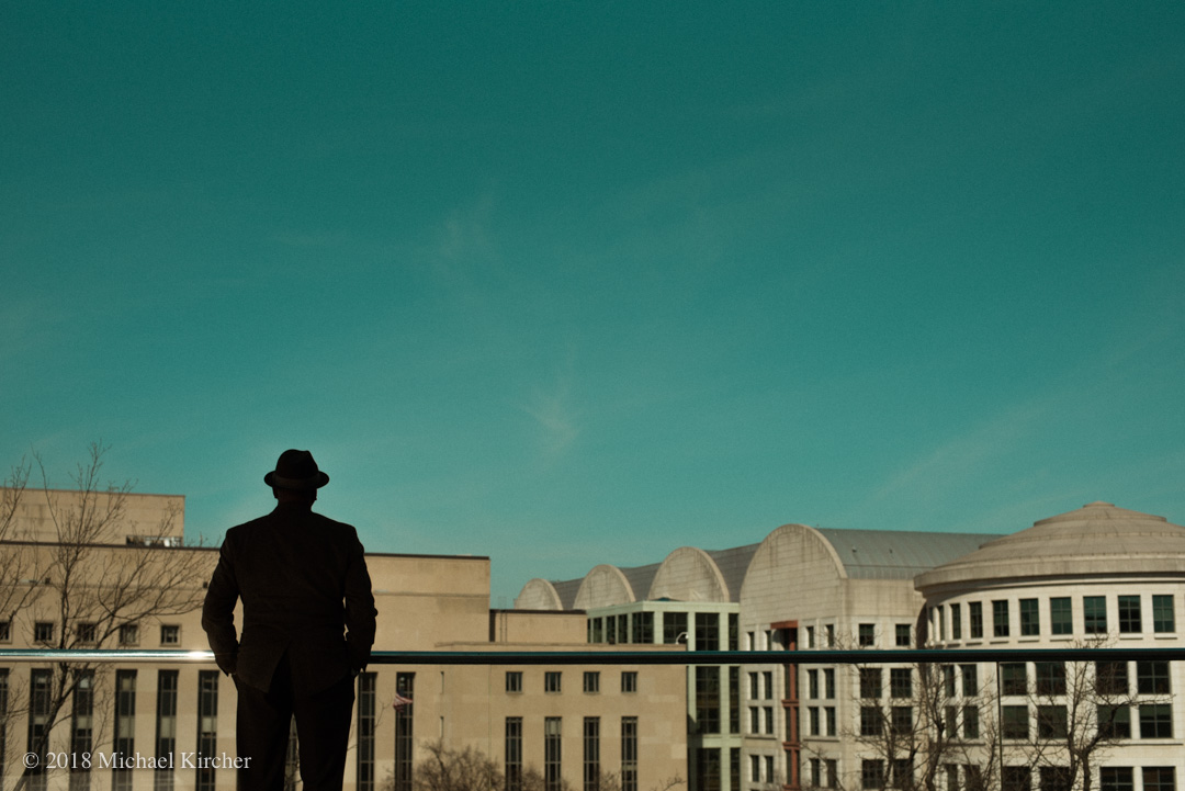 A man in a fedora stands in shadow and takes in the view from the rooftop terrace of the National Gallery of Art, East Building. Washington DC.