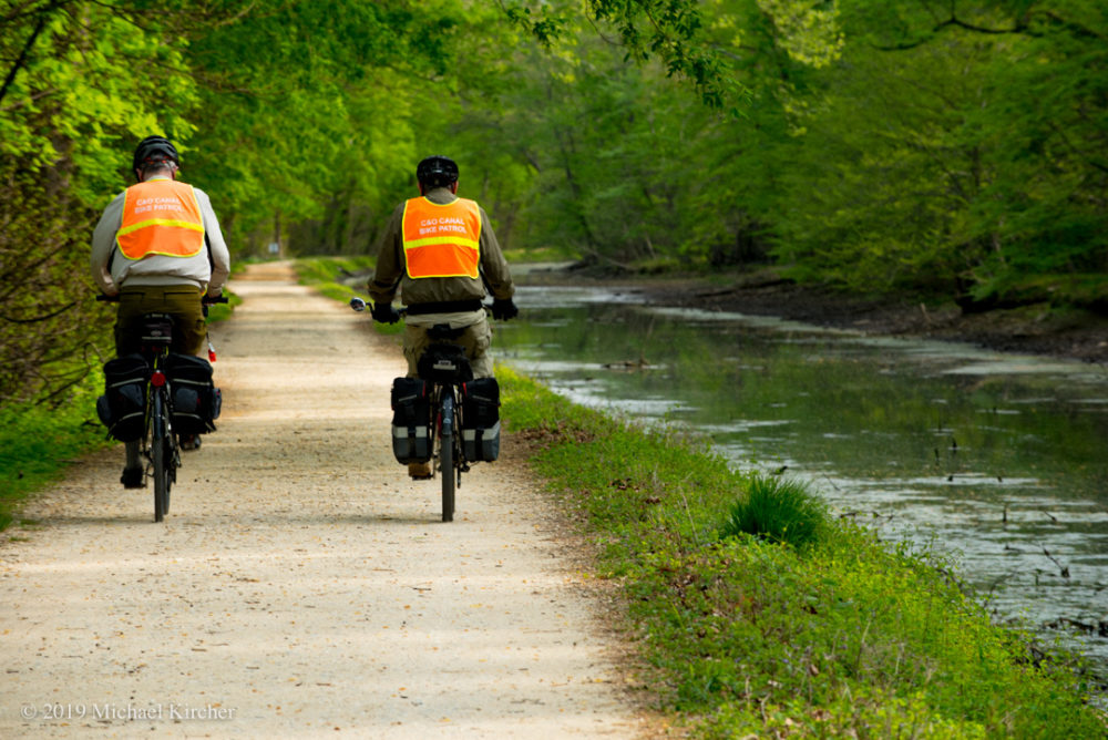 Two men on bikes with safety vests begin their volunteer bike patrol along the C&O Canal towpath.